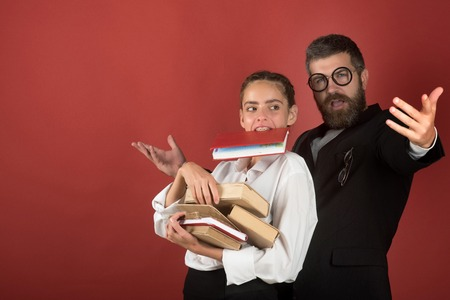 Alternative education concept. Lady and bearded man in suit and glasses. Teenager and dad hold pile of books and one in teeth. Father and schoolgirl with enthusiastic faces on terracotta background