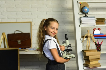 Kid does experiments. Girl with smiling face near desk with school supplies, bookshelf and blackboard. Back to school concept. Schoolgirl holds microscope on light classroom background, defocused
