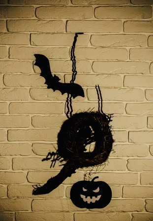 Halloween black bat, pumpkin and nest silhouette paper cutouts on beige brick wall. Holiday celebration symbols. Mystery and superstition concept.