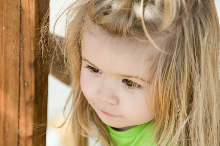 Jongen klein kind met schattig nieuwsgierig gezicht hazelaar ogen lang blond haar in groen shirt dichtbij houten kolom, geluk en jeugd concept