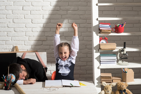 Schoolgirl with cheerful face and gestures and her sleepy dad. Girl and father on white brick background. Classroom and home education concept. Family does homework by desk with school supplies
