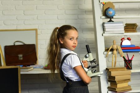 Kid does experiments. Back to school concept. Girl with ponytails and serious face expression in front of desk and shelf with school supplies. Schoolgirl holds microscope on light classroom background Stok Fotoğraf