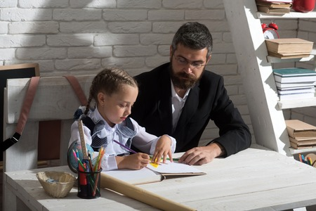 Education and family relationship concept. Schoolgirl and her dad with concentrated faces do homework. Girl and father in classroom on white brick background. Family works at desk with school supplies Stock Photo