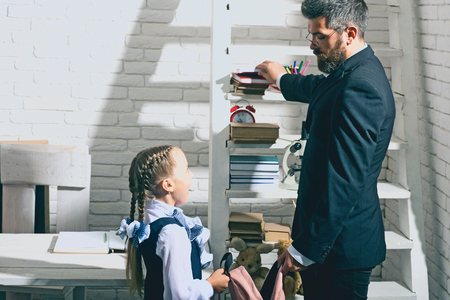 Education and family concept. Man and kid stand by shelf with school supplies. Daughter and father in classroom on white brick background. Schoolgirl and dad with happy faces put books into schoolbag