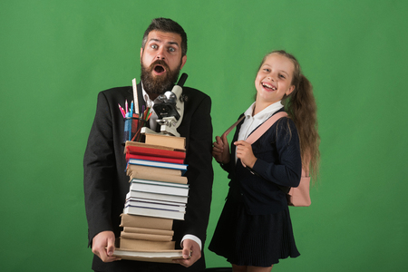 Teacher and schoolgirl with shocked and happy faces on green background. Girl and bearded man in suit. Education and back to school concept. Kid and dad hold pile of books with school supplies Zdjęcie Seryjne
