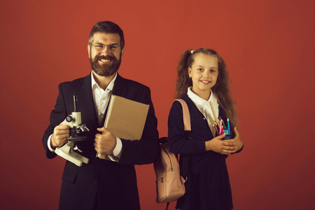 Kid and dad hold microscope, book and stationery. Home schooling and back to school concept. Father and schoolgirl with smiling faces on terracotta background. Girl and man in suit and school uniform Stock Photo