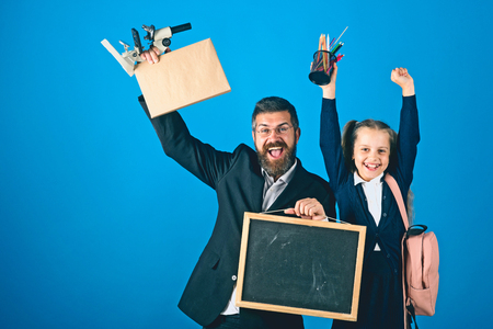 Father and schoolgirl with happy faces on blue background, copy space. Girl and bearded man in suit. Home schooling and back to school concept. Kid and dad hold school supplies and blackboard