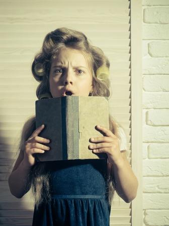 Piccolo bambino con libro. Bambino a scuola. Istruzione e infanzia. Piccola ragazza con il bigodino nei capelli. Archivio Fotografico - 84718780