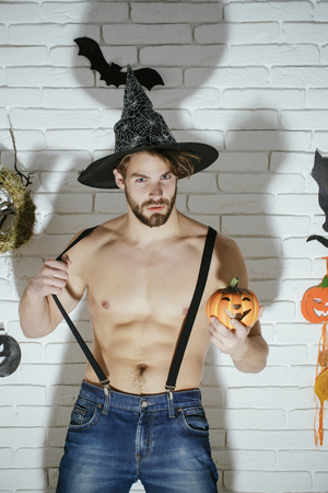 Halloween macho with muscular torso and dark shadow. Mystery and horror concept. Holiday traditional symbols on white brick wall. Jack o lantern. Man in witch hat with pumpkin. Stock Photo