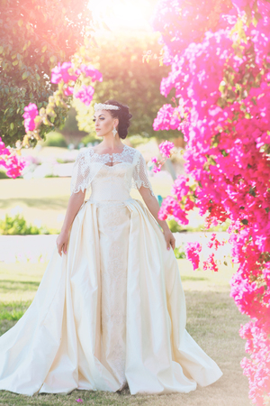 Bride in white wedding dress posing near pink bush. Marriage and happiness concept. Woman in romantic wedding dress on sunny day. Wedding dress jewelry and accessories concept.