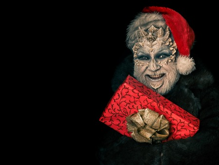 Happy monster in santa hat and fur coat. Man smiling with red present box. Sorcerer face with white eyes and sharp thorns. Elf with dragon skin and beard. New year and christmas concept, copy space