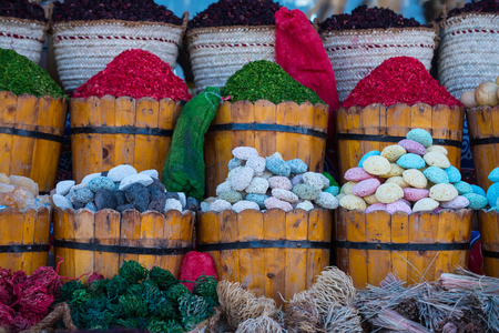 Algae pumice stones colorful green pink white and blue goods in wooden buckets and baskets for bathing and spa salons, souvenirs from arabic market Stock Photo