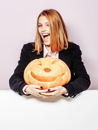 Halloween woman with happy face. Girl with orange scary pumpkin. Woman in coat and scarf at violet wall. Holiday and celebration. Party and traditional food. Stock Photo