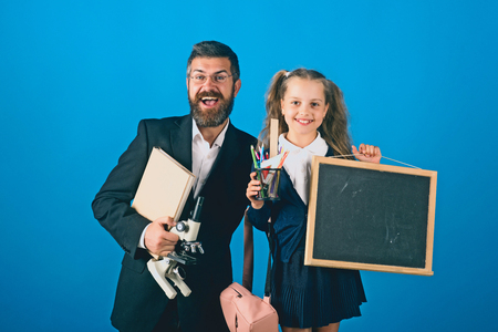 Kid and tutor hold microscope, blackboard, book and stationery. Education and back to school concept. Man and girl in uniform. Teacher and schoolgirl with happy faces on blue background, copy space
