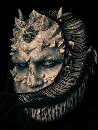 Demon hiding face with scarf isolated on black. Alien with dragon skin and grey beard. Monster with white eyes and thorns. Horror and mystery concept. Man with fictional makeup. Stock Photo