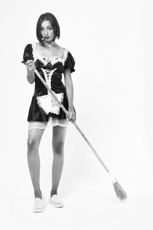 girl with pretty face in sexy maid costume with lace apron posing with sweep broom, black and white