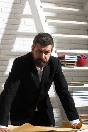 Man with beard on white brick wall background. Classic education and geography concept. Professor with strict face expression stands by desk and holds map. Teacher and school supplies in classroom