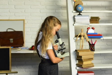 Back to school concept. Girl looks into microscope standing near desk with school supplies and bookshelf. Kid does experiment. Schoolgirl holds science class equipment on light classroom background Stok Fotoğraf