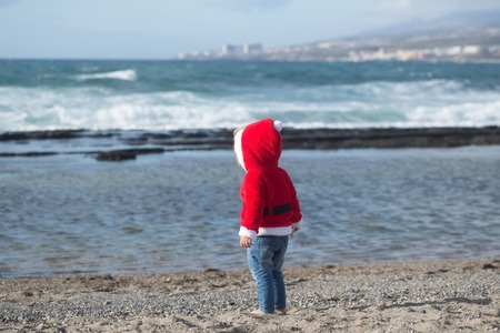 Santa baby in red costume walking barefoot on sea beach on sunny summer day on natural background. Child and childhood. Christmas and new year. Holidays celebration concept. Imagens - 84656201