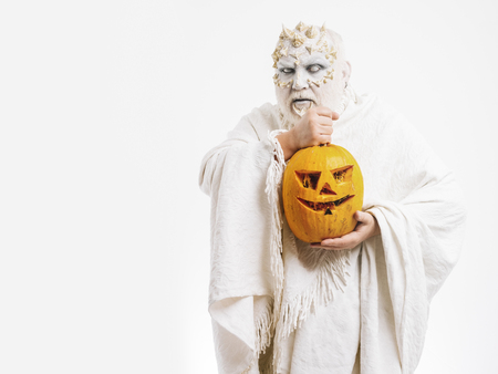 Man with orange pumpkin. Wizard with blind eyes on white background. Monster with thorns on face. Demon with silver beard and hair. Halloween and horror concept, copy space