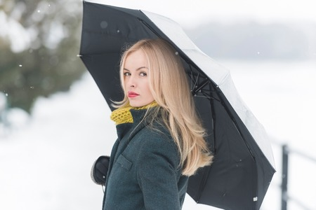 Girl with long blond hair on white snow landscape. Woman walking under umbrella on winter day. Leisure and vacation. Christmas and new year concept.