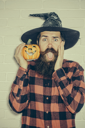 Halloween man with pumpkin on white brick wall. Jack o lantern. Holiday celebration concept. Trick or treat. Sad hipster with beard in wizard hat. Stock Photo