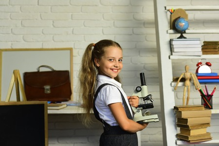 Kid does experiments. Schoolgirl holds microscope on light classroom background. Back to school concept. Girl with happy face expression in front of desk with school supplies, bookshelf and blackboard