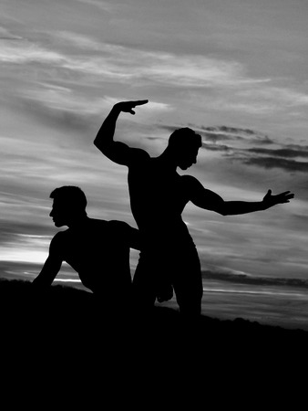 men or bodybuilders silhouettes, athlete people with sexy torso outdoor in sunset sky, black and white