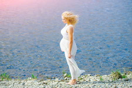 Pregnant woman in white dress walking on sea beach on sunny day on blue water. Mother with big belly expecting baby. Pregnancy and fertility. Motherhood and maternity concept