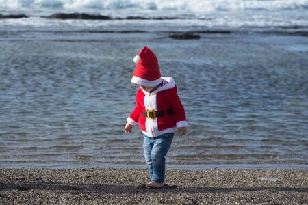 Kid in santa costume walking barefoot on sea beach on sunny summer day on natural background. Christmas and new year. Holidays celebration concept. Child and childhood Banco de Imagens