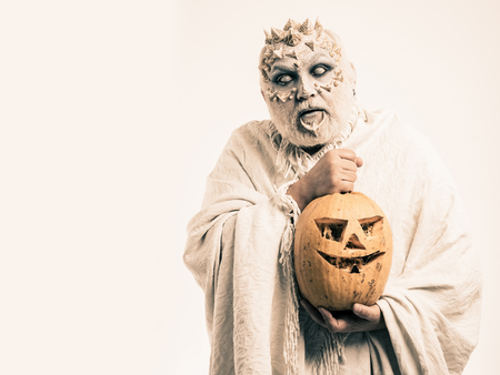 Halloween and horror concept. Demon with silver beard and hair. Monster with thorns on face. Man with orange pumpkin. Wizard with blind eyes on white background, copy space