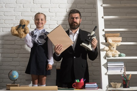Schoolgirl and dad with happy and serious faces holding teddy bear, book and microscope. Kid and man stand by school supplies. Girl and teacher on white brick background. Education and family concept