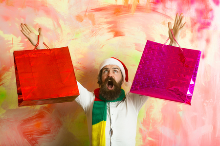 Xmas package or shopping pack. Holiday and celebration. New year guy with in scarf and hat. Christmas man with happy face. Santa claus man with present or gift.