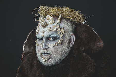 Autumn and harvest concept. Man with hay wreath on head. Demon in fur coat on black background. Alien or reptilian makeup with sharp thorns and warts. Monster with dragon skin and bearded face.