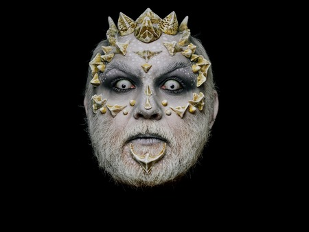 creepy alien: Monster face with scary look of white eyes. Alien or reptilian makeup with sharp thorns and warts. Demon head isolated on black. Horror and fantasy concept. Man with dragon skin and beard.