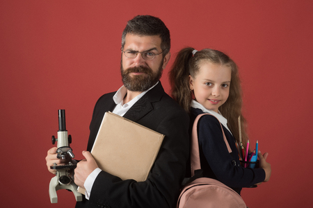 Father and schoolgirl with proud and happy faces on terracotta background. Family and home schooling concept. Girl and man in suit and school uniform. Kid and dad hold microscope, book and stationery