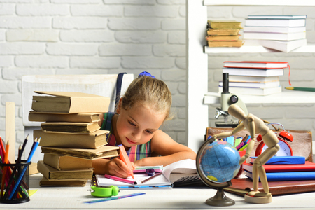 Schoolgirl with concentrated face draws in art book. Back to school concept. Kid near pile of textbooks and school supplies on white brick background. Girl with globe and colorful stationery on table