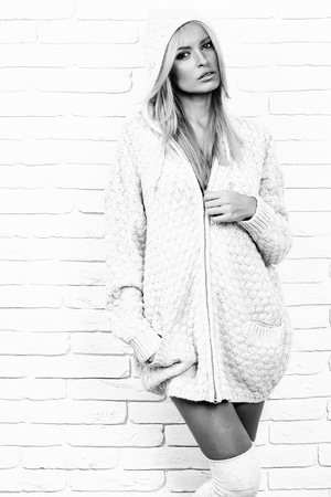 girl fashion model with blond hair in sexy knitted sweater poses on brick wall background, black and white