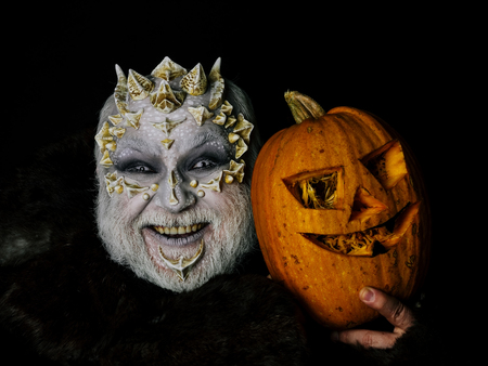 Horror and halloween concept. Demon in fur coat on black background. Man laughing with pumpkin. Alien or reptilian makeup with sharp thorns and warts. Monster with dragon skin on scary face. Stock Photo