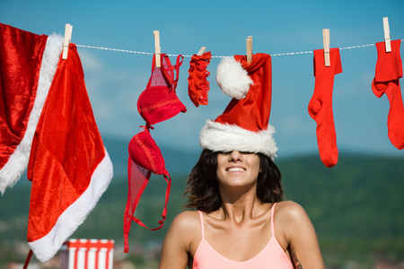 Xmas red costume on rope with pin. Laundry and dry cleaning. New year girl on sunny blue sky. Christmas woman with happy face outdoor. Santa claus girl hanging clothes for drying. Banco de Imagens