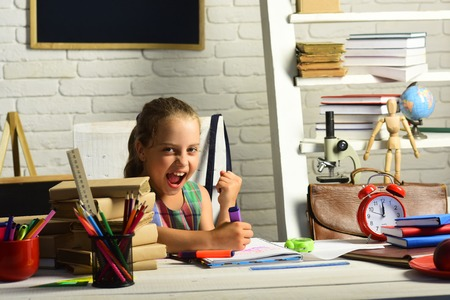 Childhood and back to school concept. Kid with colorful stationery on white wall background. Girl with happy face does homework. Pupil with books and school supplies.