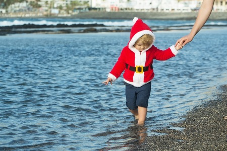 Child holding female hand. Christmas and new year. Mothers day and family love. Winter holidays celebration concept. Boy in santa costume walking on sea beach. Imagens - 85251687