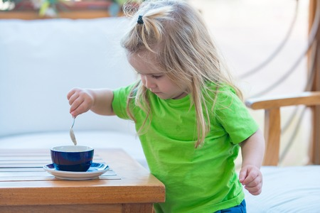 Child boy with blond long hair mixing sugar with teaspoon. Little kid boy making tea. Boy child mixing sugar in blue cup. Healthy breakfast for child. Childhood and baby care concept. Stock fotó