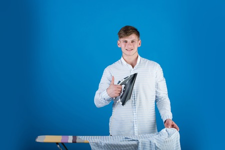 Guy using iron. Ironing board on blue background. Housework and fashion concept. Man ironing clothes. Macho wearing striped shirt. Stock Photo