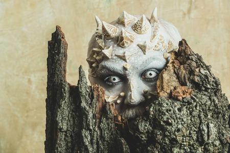 날카로운 가시와 사마귀가있는 괴물. 드래곤 피부와 수염 난 얼굴을 가진 남자. 머리에 뿔 고블린입니다. 베이지 색 벽에 오래 된 나무 껍질 뒤에 사제.