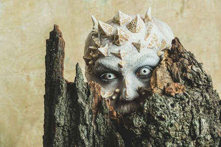 Monster with sharp thorns and warts. Man with dragon skin and bearded face. Goblin with horns on head. Druid behind old bark on beige wall. Tree spirit and fantasy concept.