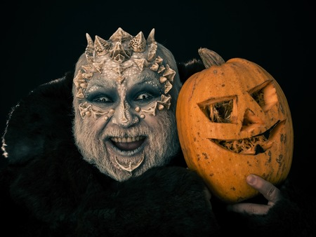 creepy alien: Monster with dragon skin on scary face. Alien or reptilian makeup with sharp thorns and warts. Demon in fur coat on black background. Horror and halloween concept. Man laughing with pumpkin.