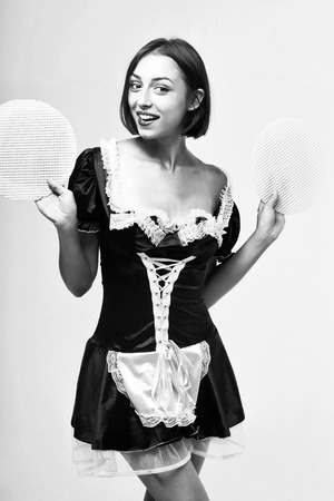 woman with smiling face in beautiful sexy lace servant uniform holding cake layers in hands posing, black and white