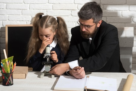Girl and man sit by desk and looks into microscope. Teacher and schoolgirl in study room on white brick background. Kid and tutor with busy faces. Home schooling, science and back to school concept Stock Photo