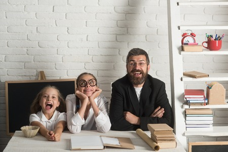 Girls and bearded man sit at desk with books. Teacher and schoolgirls on classroom background. Kid, older sister and their tutor with happy and dreamy faces. Home schooling and back to school concept Reklamní fotografie